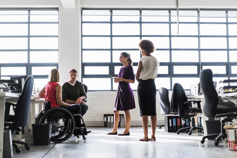 A photo of business team communicating at workplace. Female sitting on wheelchair in meeting. They are in brightly lit n creative office.